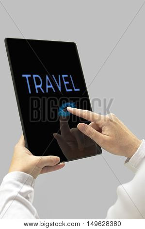 Travel message on digital tablet computer display. Woman hands with tablet computer. Selective focus.