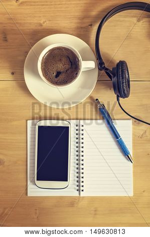 Notebook with pencil coffee cup blank screen smart phone and headphones on wooden table business concept. Selective focus.
