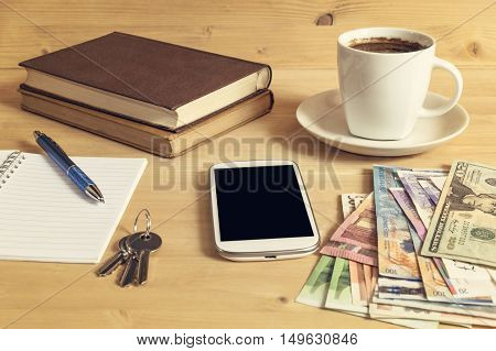 Still life photo of smartphone notebook coffee book pencil money and keys on wooden table. Selective focus.