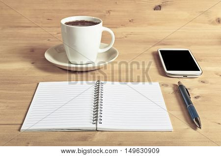Still life photo of smartphone notebook coffee and pencil on wooden table. Selective focus.
