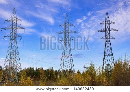 High-voltage electric lines and electric poles in the field in the fall