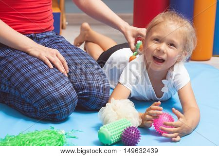 Shot of a child lying on the floor during an integration therapy session