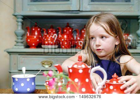 Cute Little Girl Preparing Tea In Teapot