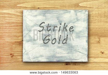 Vintage hipster motivational phrase note Strike Gold sign