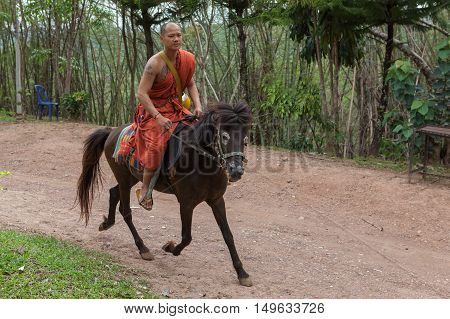 Chiang Rai, Thailand - May 21, 2016: Young Buddhist Monk Fast Riding A Horse In Golden Horse Temple