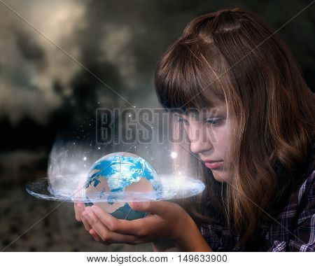 Girl holding a glowing planet earth. The concept of ecology climate destruction the future of humanity