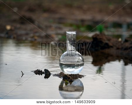 Chemical glassware retort stands in a puddle of dirty water. Concept - water pollution environment ecology