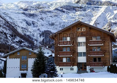 Swiss Alps:Modern wooden houses on a background mountains  in the charming Swiss resort of Saas-Fee, Switzerland