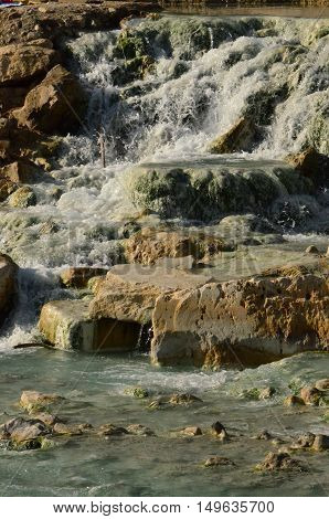 Saturnia hot springs with a waterfall in Tuscany Italy.