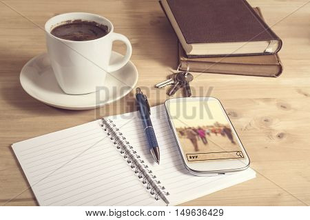 Still life photo of smart phone with travel search notebook coffee book pencil and keys on wooden table. Selective focus.