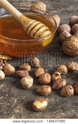 Bee honey in a glass jar hazelnuts and walnut on an old vintage wooden table. Healthy eating style concept. Selective focus.