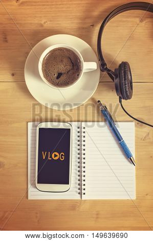 Smart phone with headset notebook pencil coffee cup on wooden table vlog concept. Selective focus.
