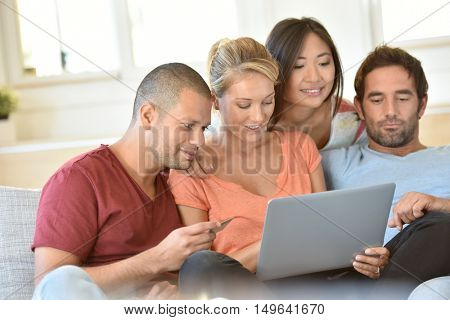 Friends sitting together in couch websurfing on laptop computer