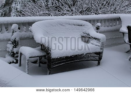 Snow covered patio couch, table and small tree on deck