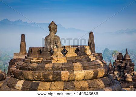Ancient Buddha statue and stupa at Borobudur temple in Yogyakarta Java Indonesia.