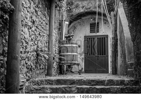 Black And White Image With Wine Press And Closed Doors. Old Italian Wooden Wine Press For Pressing G