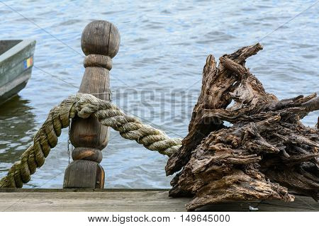 Rope Knotted Along A Ship Bollard. Docks With Rope In Harbor, Blue Background And Boat Fragment..