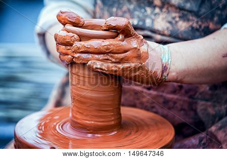 hands of a potter creating an earthen jar on the circle