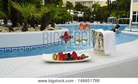 Romantic photo of champangne and fruits in the pool background. Still life.