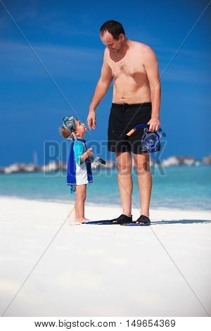 Father with his son having fun on the beach and getting ready to snorkle in Maldives
