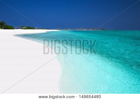 Tropical island with sandy beach palm trees overwater bungalows and turquoise clear water on Maldives Island