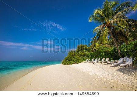 Tropical island with sandy beach palm trees overwater bungalows and tourquise clear water on Maldives island