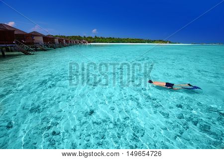 Young man snorkeling in tropical island with sandy beach palm trees overwater bungalows and turquoise clear water