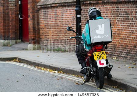 YORK, UK-SEPTEMBER 28, 2016.A motorcyclist from the increasingly popular take away delivery company Deliveroo parked at the side of city streets waiting for a hot food delivery from take aways and restaurants to take to people's homes.