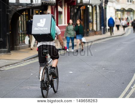 YORK, UK-SEPTEMBER 28, 2016.A cyclist from the increasingly popular take away delivery company Deliveroo speeding through city streets with a hot food delivery from take aways and restaurants to homes.