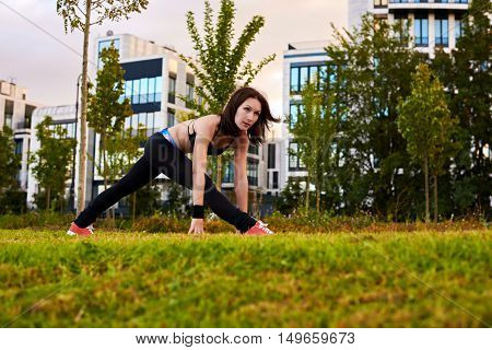 Athletic woman with strong body making fitness exercises outdoor on the green and yellow grass near modern house. Sport health life concept. Yoga female watch into camera.