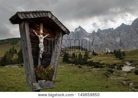 Religious cross in the karwendel alps in autumn with dramtic dark sky.