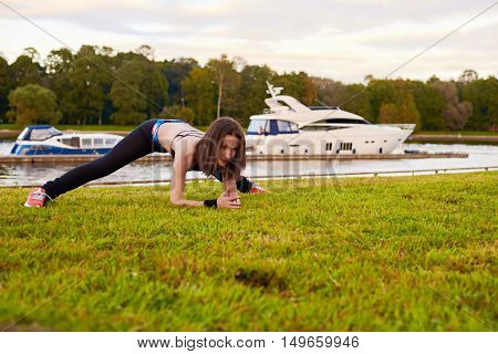 workout back legs arms body and head in the fresh air. outdoor training on grass on beach in autumn evening or morning. Sport theme wwith copy space for logo or advertising text.