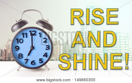 Rise and Shine text with blue alarm clock