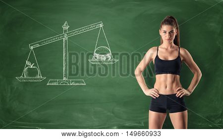 Slim girl on the background of painted scales, where an apple outweighed a burger. Choose between fruits and fast food. Concept of weight loss, healthy lifestyles, diet, proper nutrition.