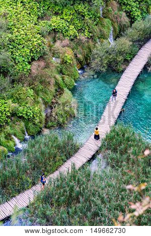PLITVICE CROATIA - SEPTEMBER 15: Detailed view of a bridge in Pltivice lakes with tourists walking along on September 15th 2016 in Plitvice