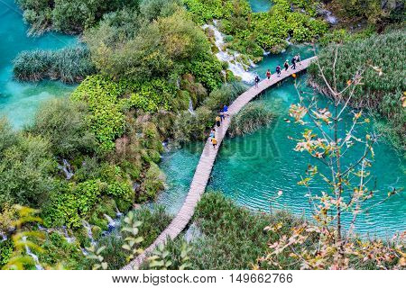 PLITVICE CROATIA - SEPTEMBER 15: Aerial view of Plitvice lakes a famous world heritage sights with people walking along a bridge on September 15th 2016 in Plitvice