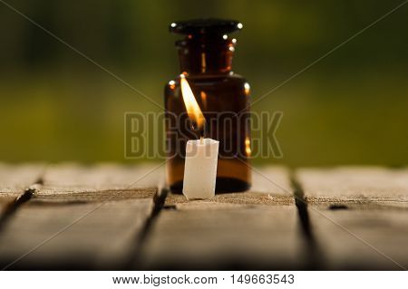Small brown medicine bottle for magicians remedy and white wax candle sitting on wooden surface, beautiful night light setting, magic concept.
