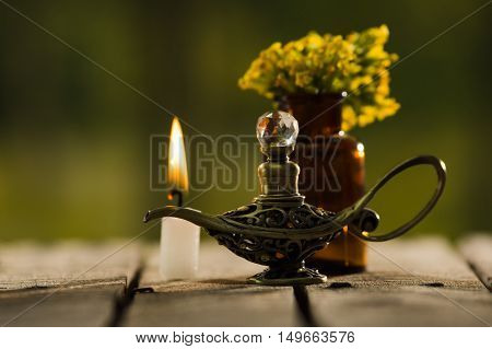 Small brown medicine bottle for magicians remedy, Aladin type lamp and white wax candle sitting on wooden surface, beautiful night light setting, magic concept.
