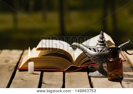 Thick book lying open on wooden surface, Aladin lamp and wax candle sitting next to it, beautiful night light setting, magic concept shoot.