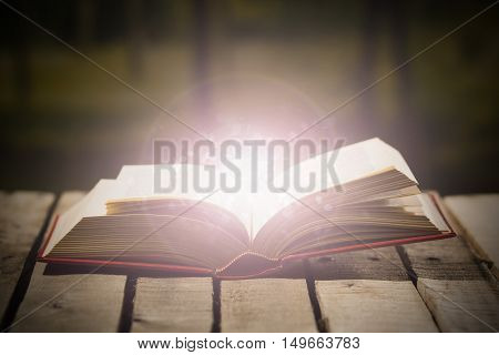 Thick book lying open on wooden surface, glowing animated star dust coming out, beautiful night light setting, magic concept shoot.