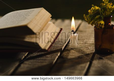 Thick book lying open on wooden surface, wax candle and small bottle with yellow flowers sitting next to it, beautiful night light setting, magic concept shoot.