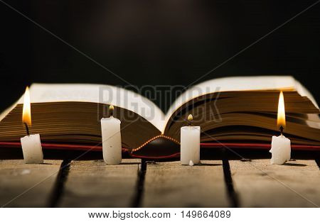 Thick book lying open on wooden surface, wax candles placed in front, beautiful night light setting, magic concept shoot.