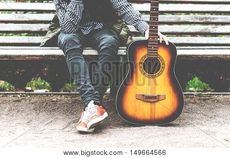 young man sitting in the park on a bench with a guitar