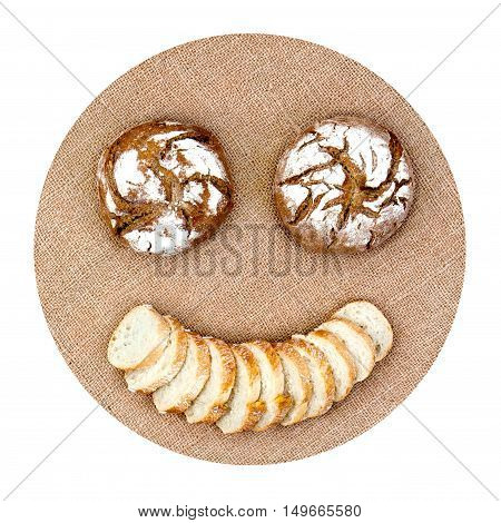 Smiling emoticon with round bread and slices on hemp canvas representing diet healthy food