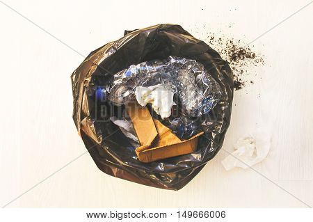 Trash can with black bag and debris on the white floor