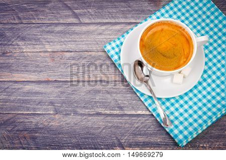 Cup of hot morning coffee on saucer with sugar and spoon wooden board in rustic style