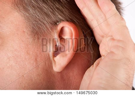 Ear of a man close up with hearing aid. The man is cupping his hand behind his ear.