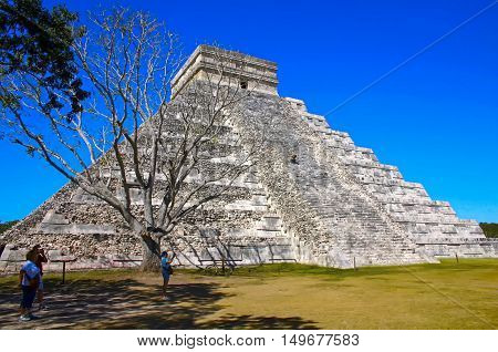 Kukulcan pyramid behind the dead tree with a blue sky in Chichen Itza Mexico