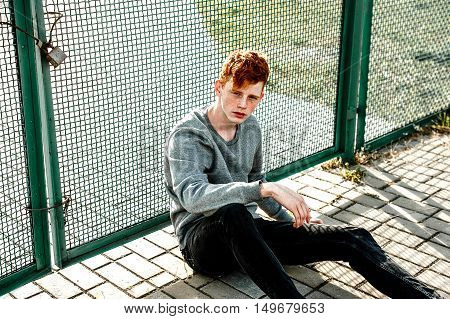 One Young Handsome Red Haired Fashionable Boy Sitting Near Stadium In Sunny Day Outdoor , Wearing Ca