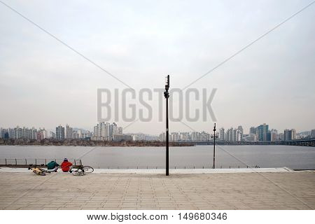 SEOUL SOUTH KOREA JANUARY 06: People sitting by the famous Han river which is a landmark where many go to cycle along the river January 06th 2016 in Seoul